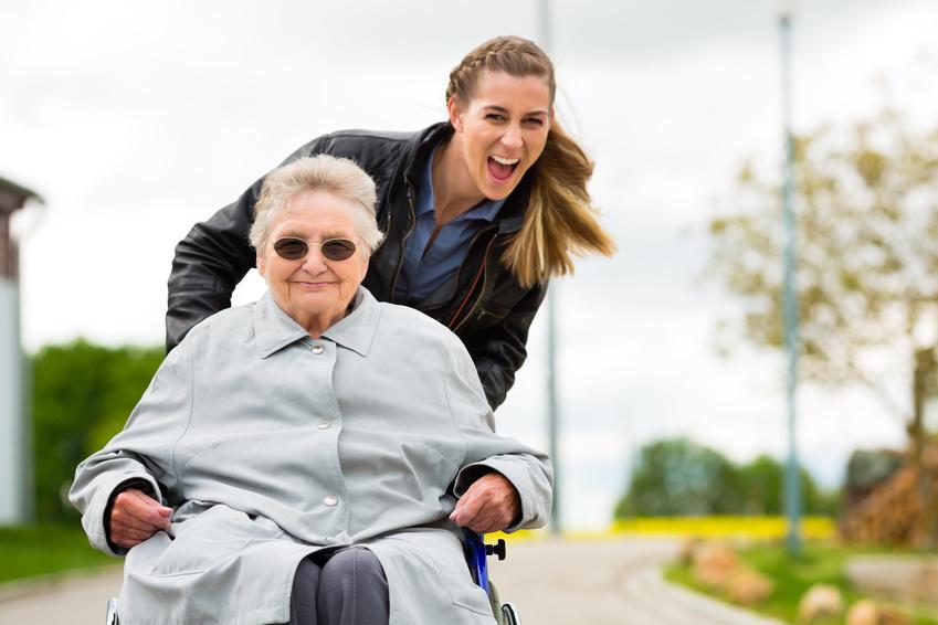 Seniorin im Rollstuhl geschoben von junger Frau